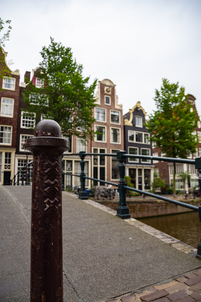 A canon on a bridge in Amsterdam with houses in the background