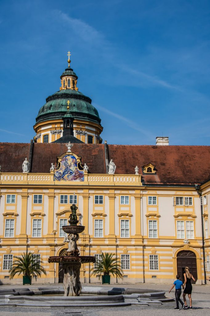 A fountain in a courtyard surrounded by the buildings of Melk Abbey