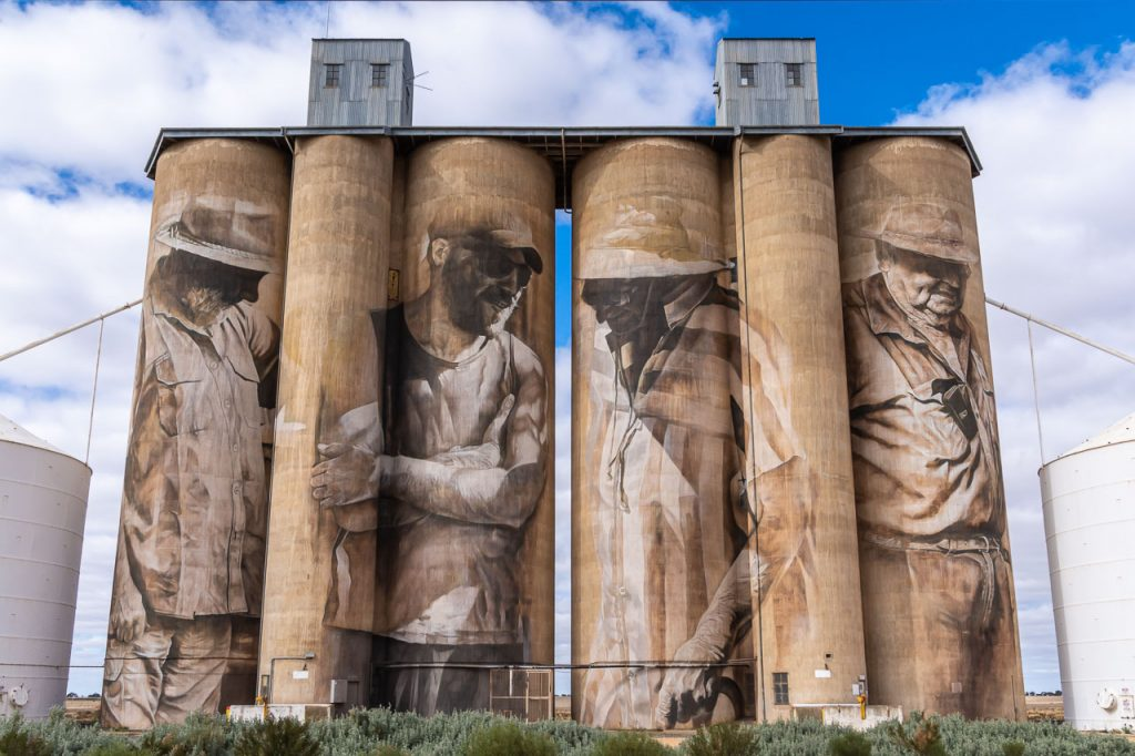 Paintings on 3 men and 1 woman farmers on concrete grain silos