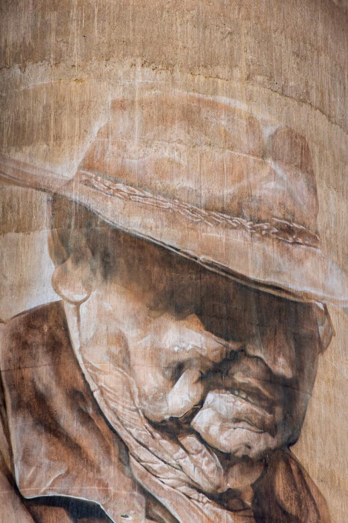 Sepia-coloured painting of old man on a concrete grain silo