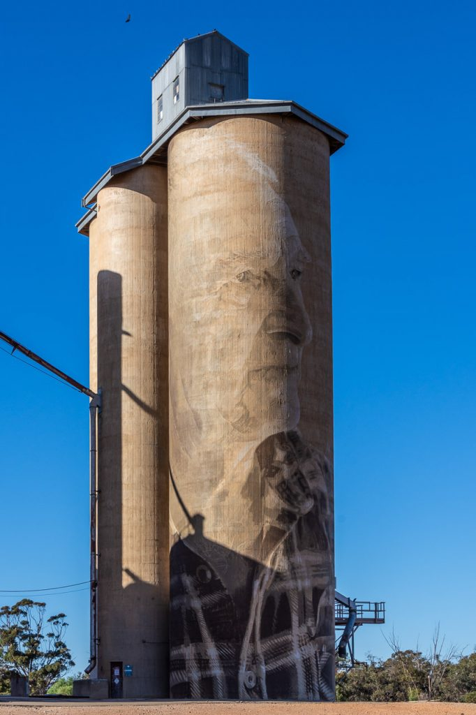 Sepia-coloured painting on concrete grain silo of local male farmer from Lascelles