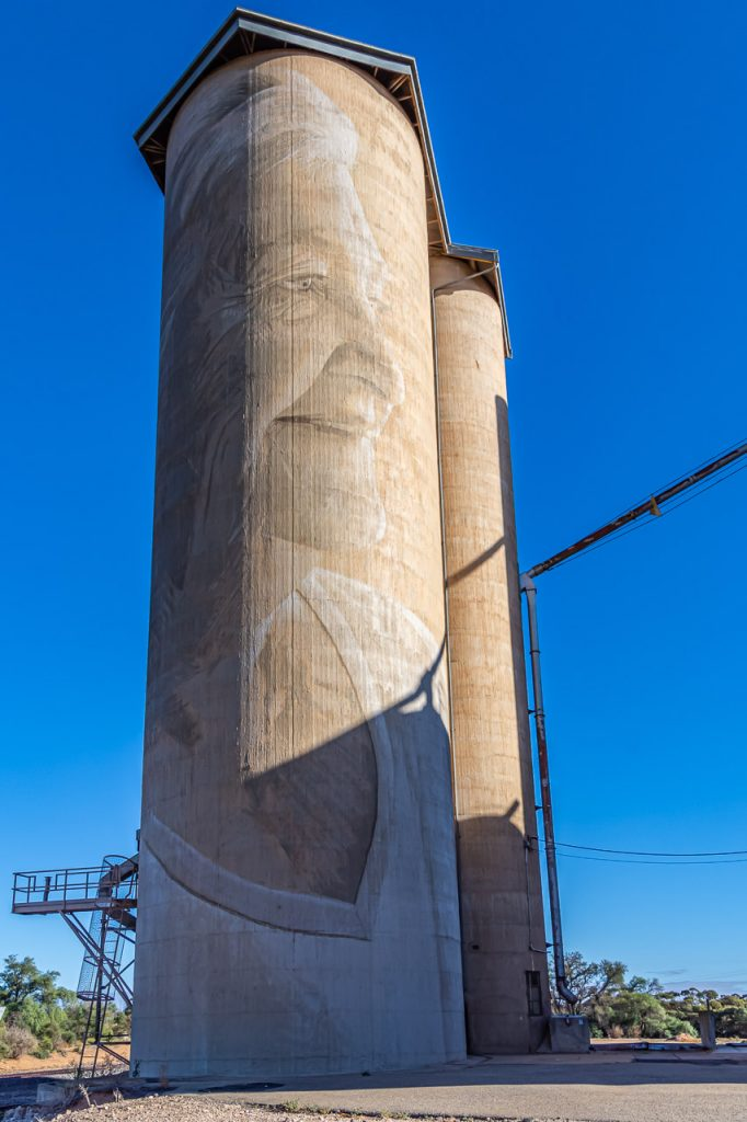 Sepia-coloured painting on concrete grain silo of local female farmer from Lascelles