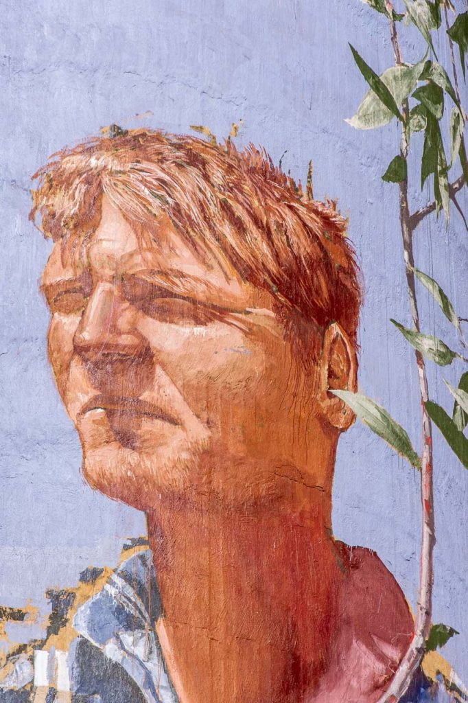 Coloured painting of the face of a young man on a concrete grain silo