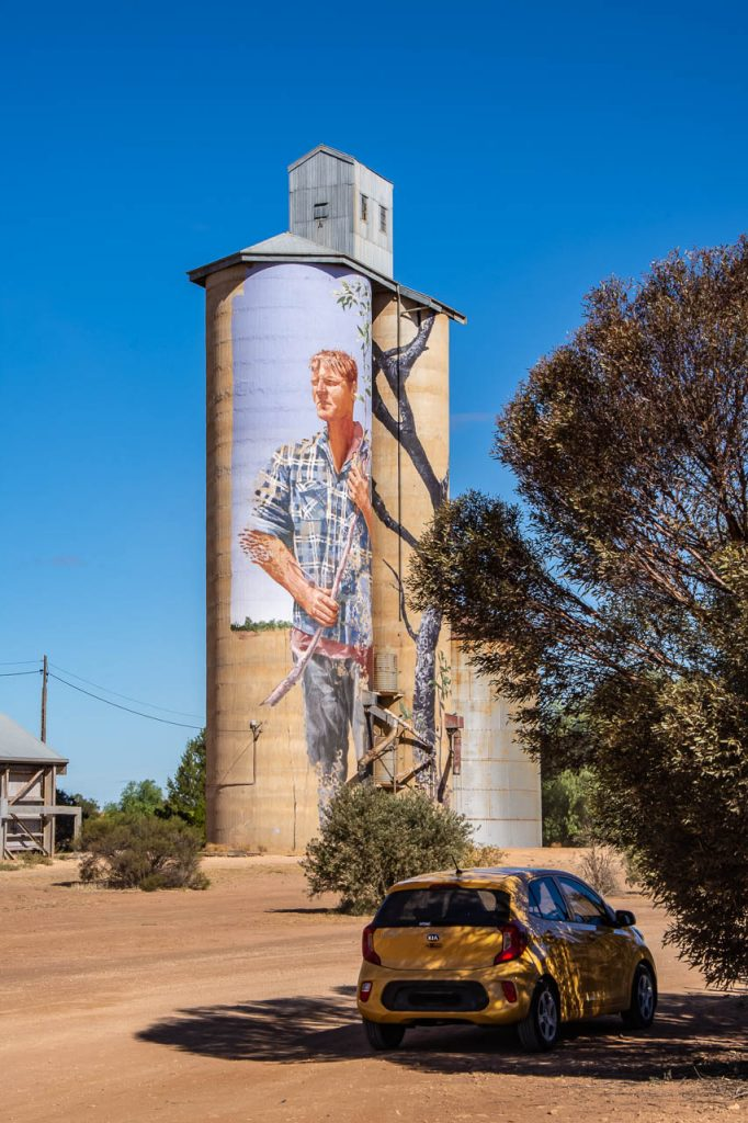Painting of your man on concrete grain silo and yellow car near silo
