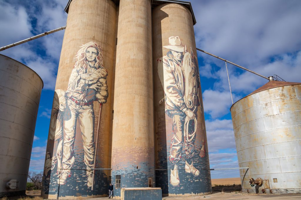 Painting of cowgirl, horseman and horse on concrete grain silo