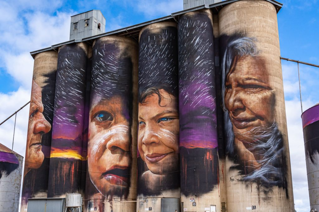 Brightly coloured painting of 4 Australian Aboriginals on concrete grain silos