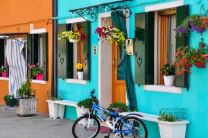 Coloured house with hanging baskets of flowers and bicycle in front