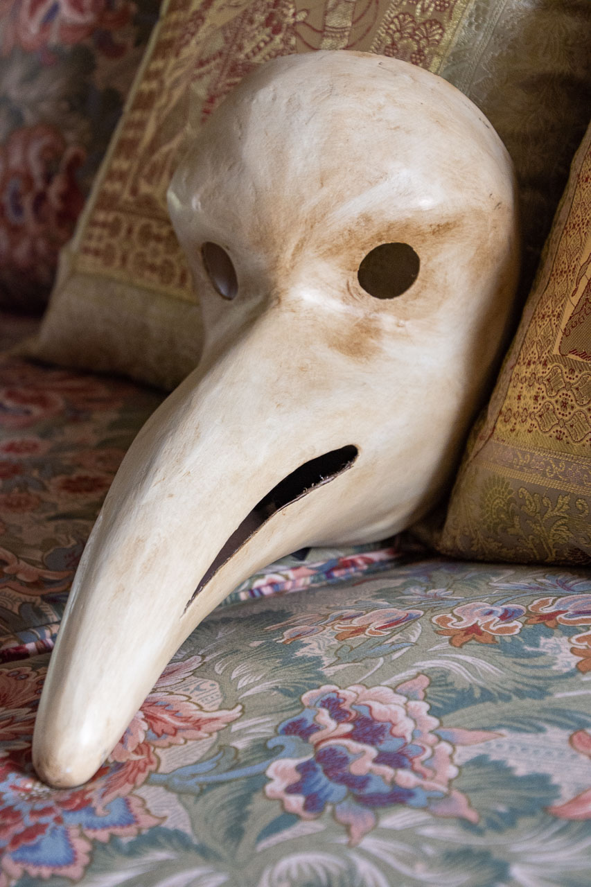 A white mask with open eyes and a long nose