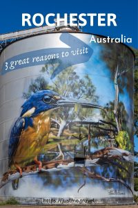 A painting on a metal grain storage silo of a blue and yellow bird with a long narrow beak. The painting includes a river and a bridge behind the bars.