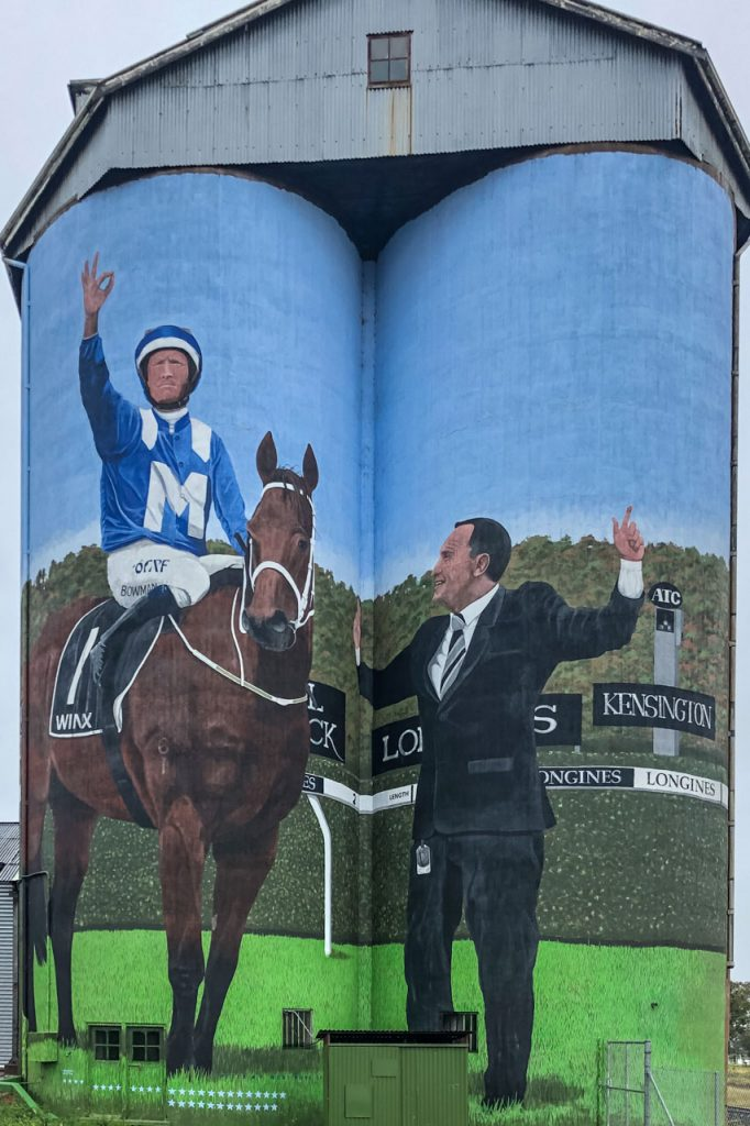 Painting on silos of a jockey on a horse with the training standing next to the horse