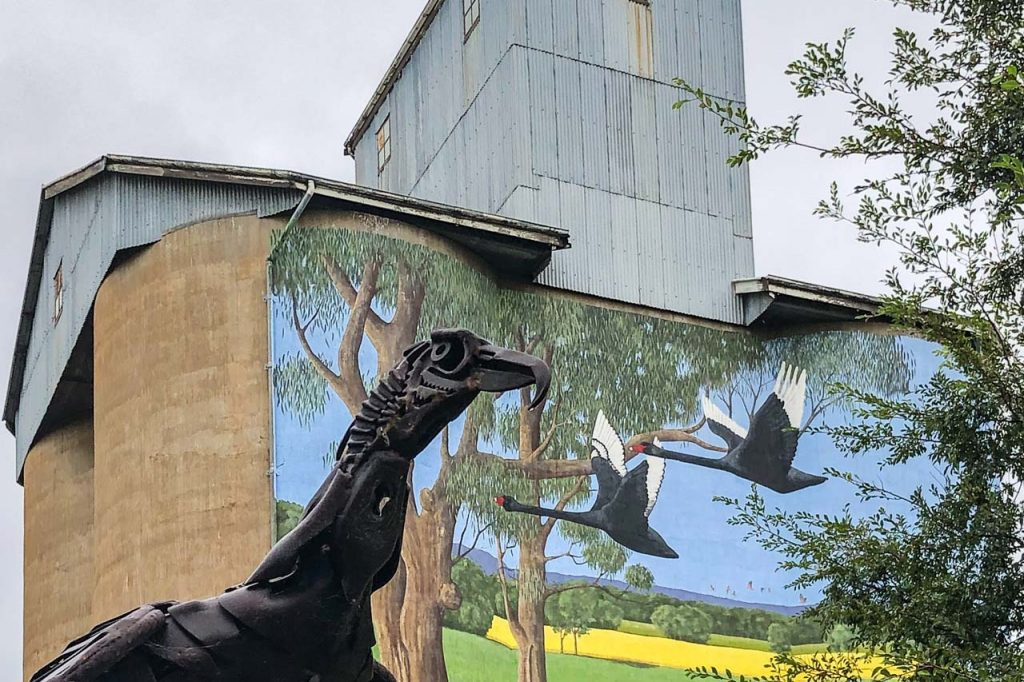 A sculpture of a bird made from recycled metal. A painting on grain silos of flying black swans is behind the sculpture.