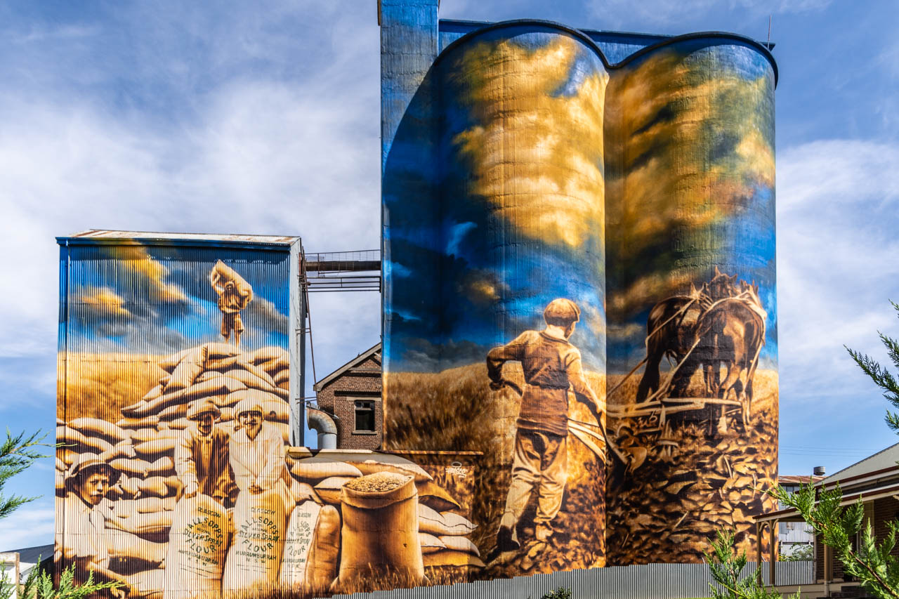 A painting on grain silos of a boy, two ladies and a man holding bags of wheat, and a man ploughing a paddock with 2 horses