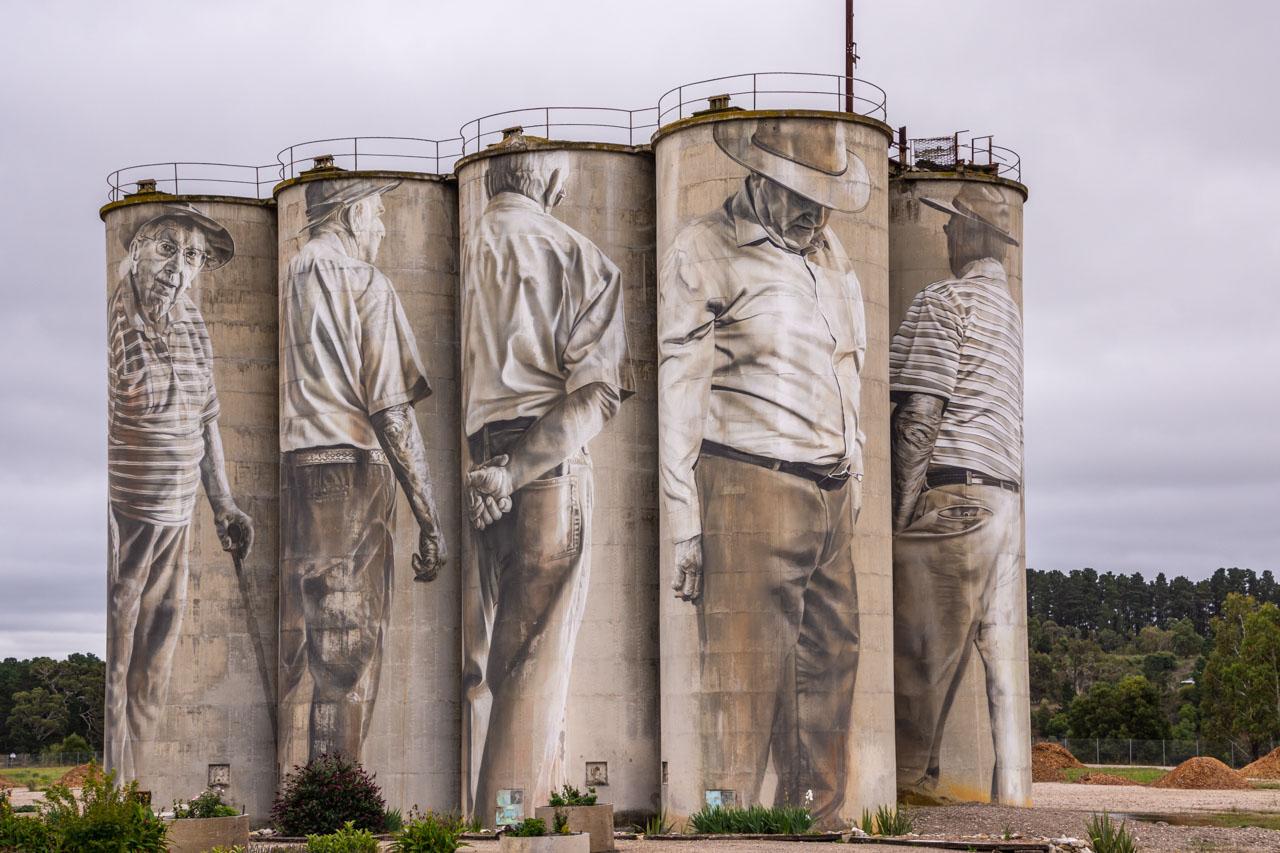 Five elderly men painted on five silos