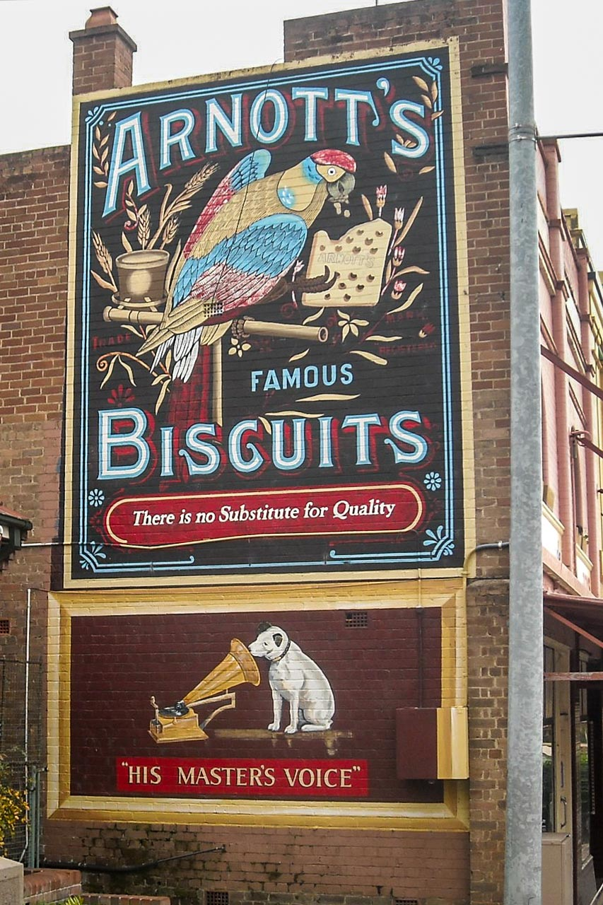 Painting on a brick wall of a parrot eating a biscuit, and painting of a dog and a gramophone.