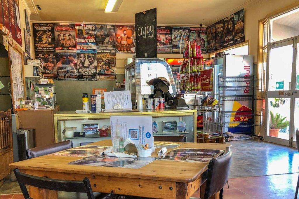 Table and chairs and counter inside a shop with boxing posters on the walls.