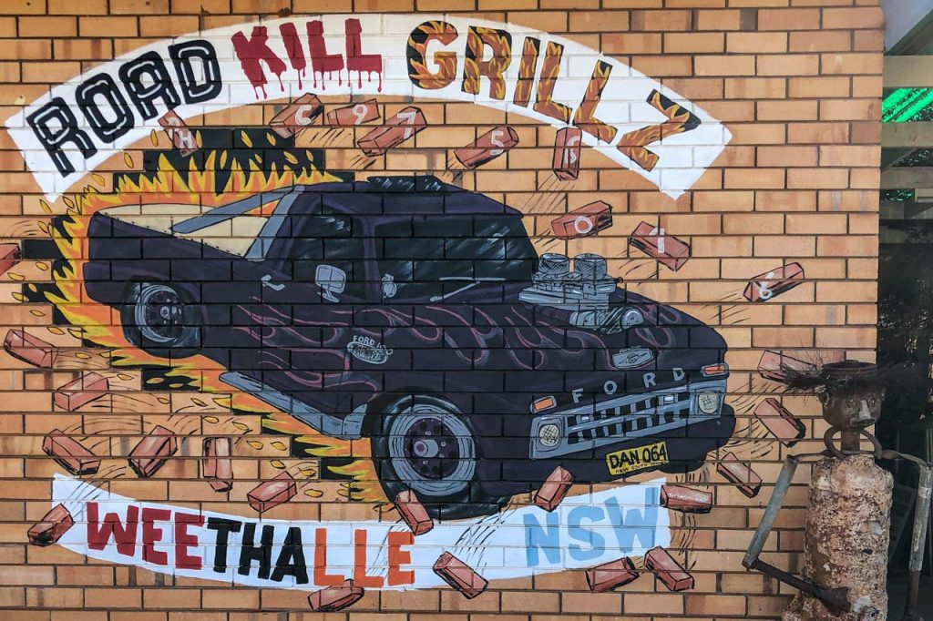 """Painting on a brick wall of a truck with writing around it saying, """"Road Kill Grillz Weethalle NSW"""""""
