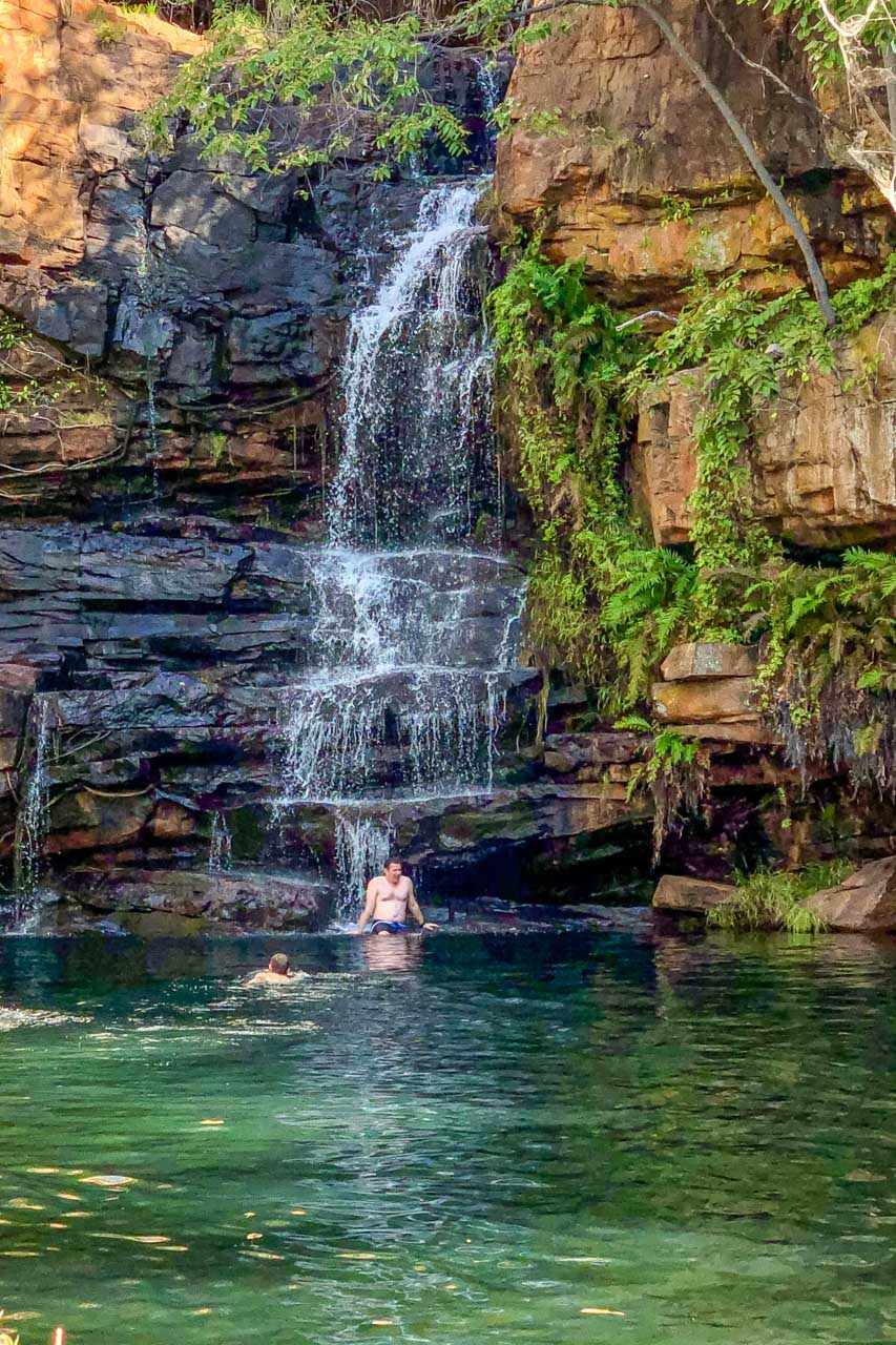 A man sitting under a waterfall and a man swimming uptown the waterfall
