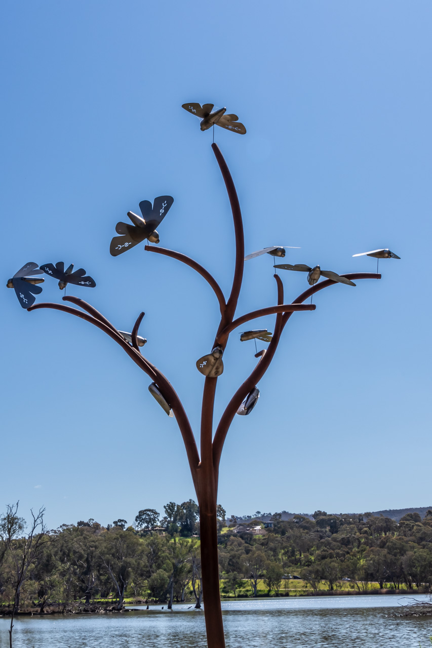A metal tree with metal moths attached to the tree
