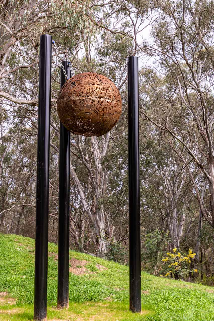 A decorative metal ball hanging from chains on three poles