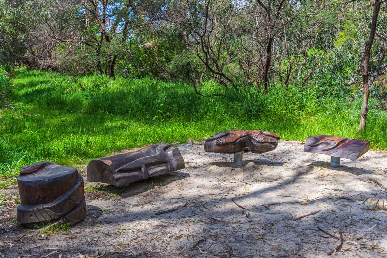 Wooden seats in the shape of animals surrounded by grass and trees