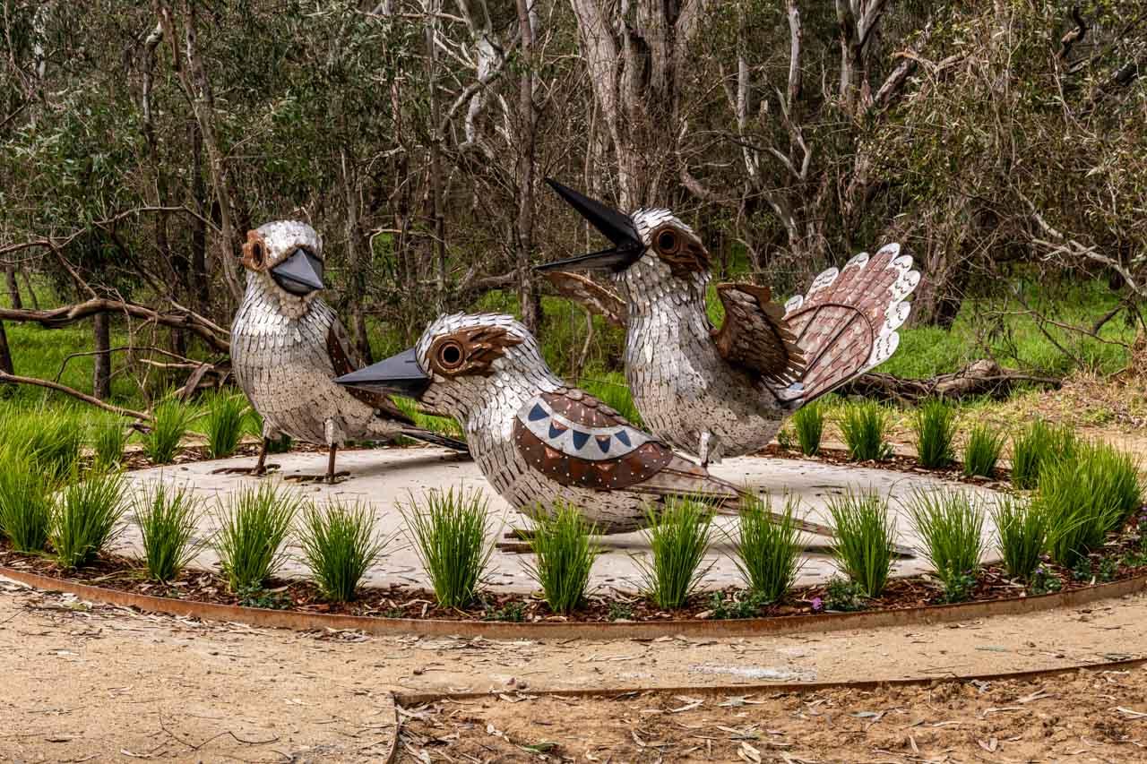 Three large metal kookaburras with the bush behind them