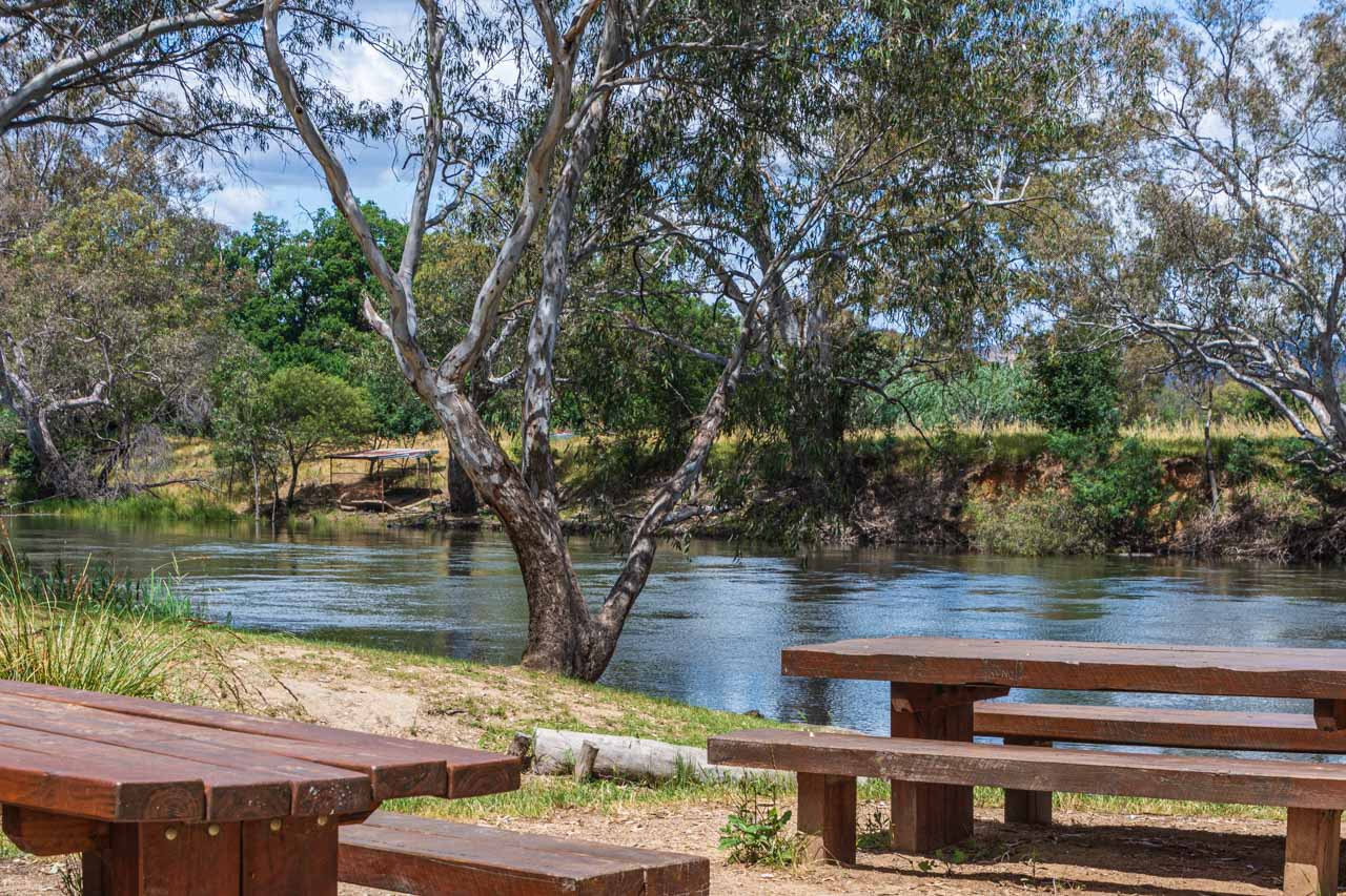 A photo of wooden picnic tables and benches on the banks of a river
