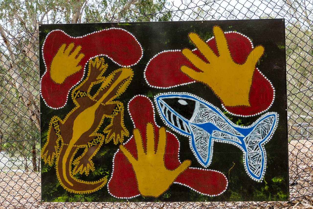 a painting of a fish, a goanna, and hands prints