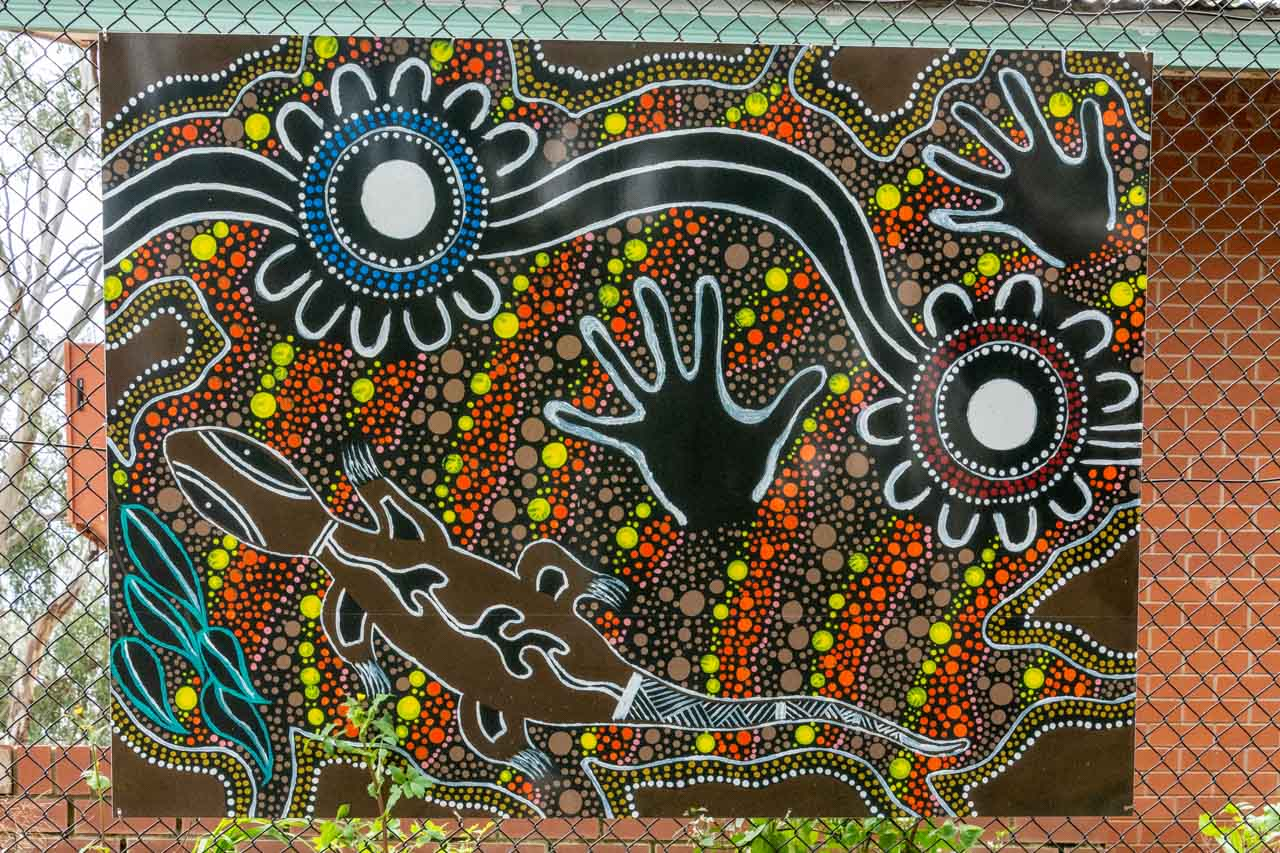 A dot painting of a goanna and hand prints