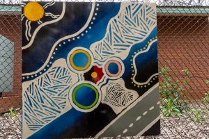 A painting of a road, the sun, and the Aboriginal flag