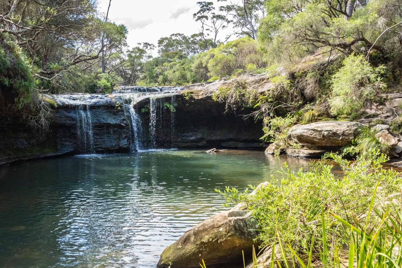 Water cascading over a rock ledge into a natural swimming hole
