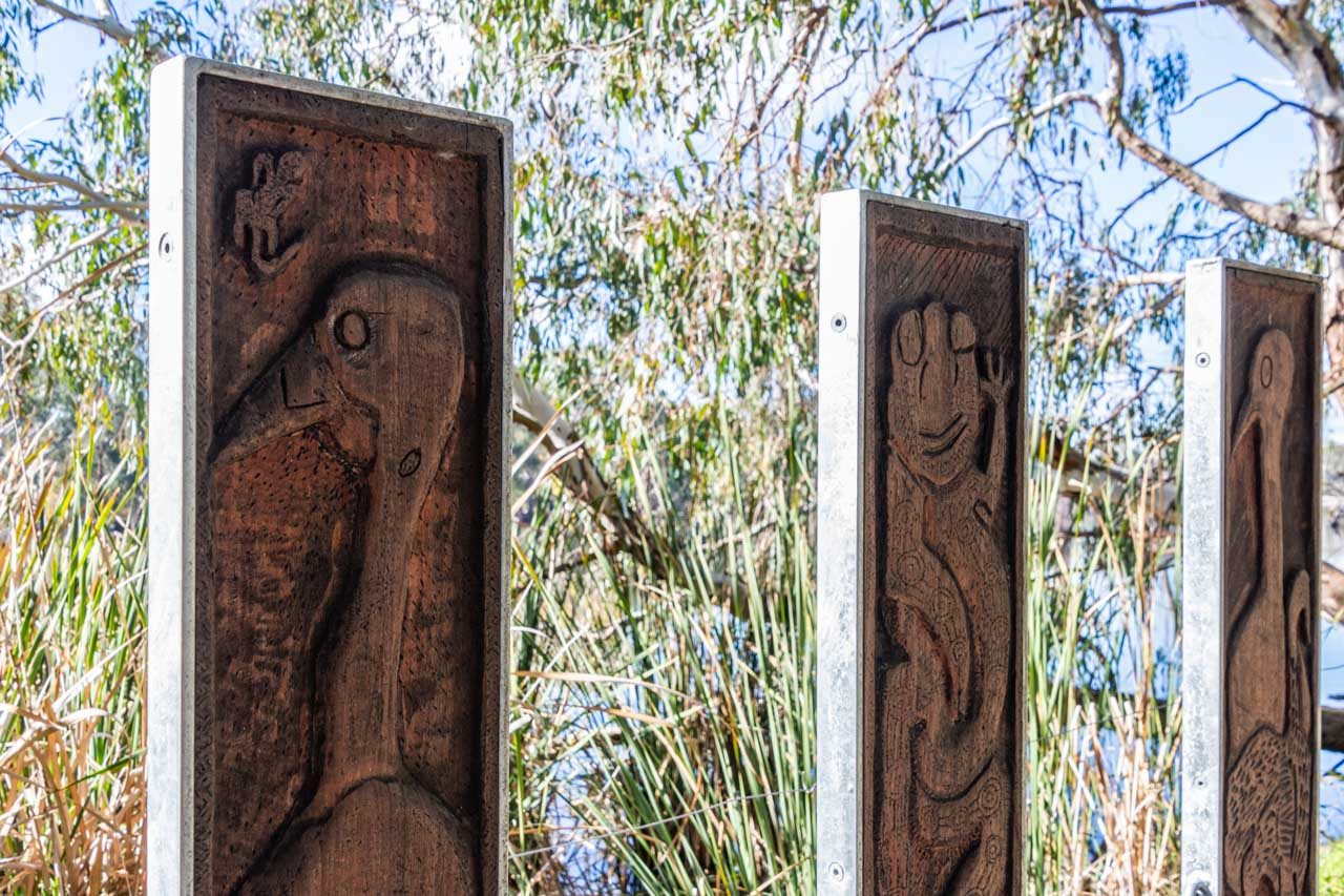 Three wooden poles with animals carved on them