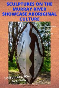 The image is of a metal shield with writing telling you sculptures showcase Aboriginal culture