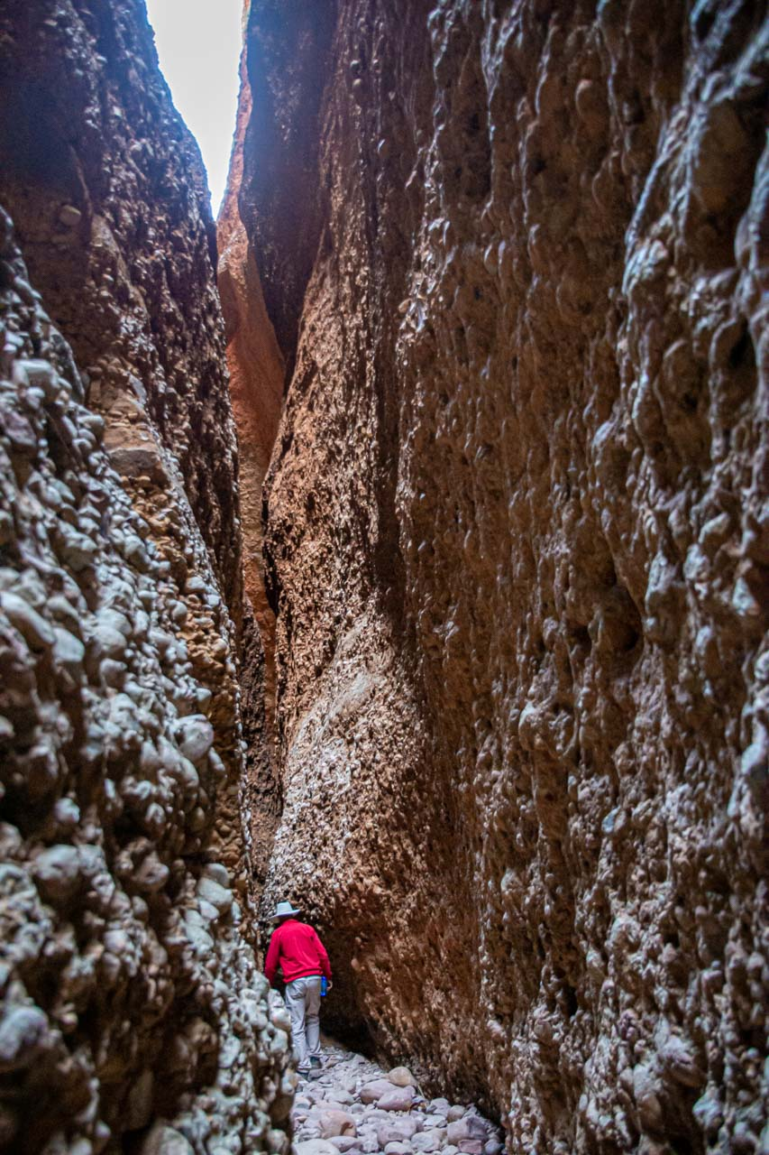 A man walking on a rocky path between very high cliff walls