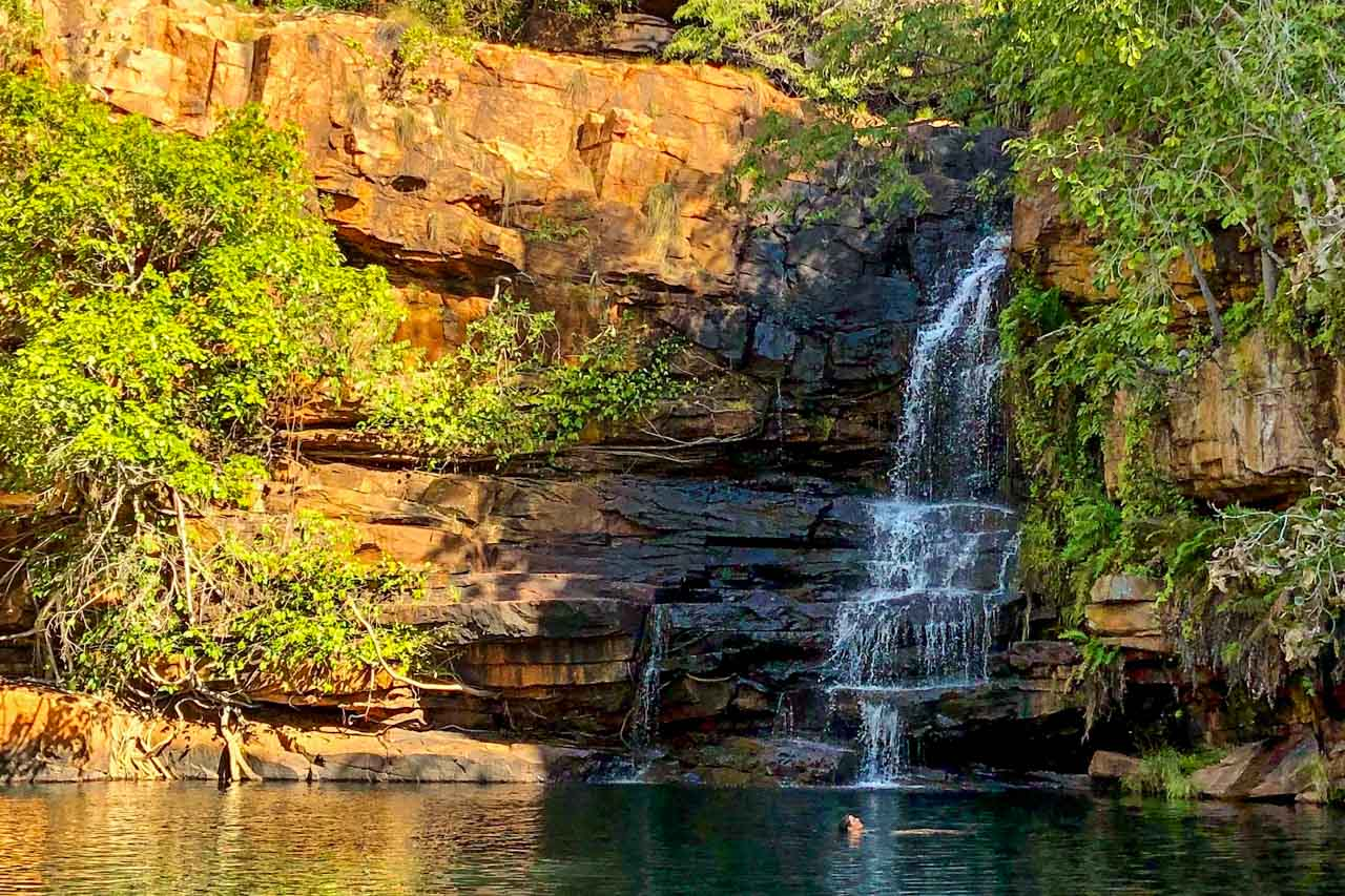 A lady swimming in a rock pool with a waterfall flowing down the rocks