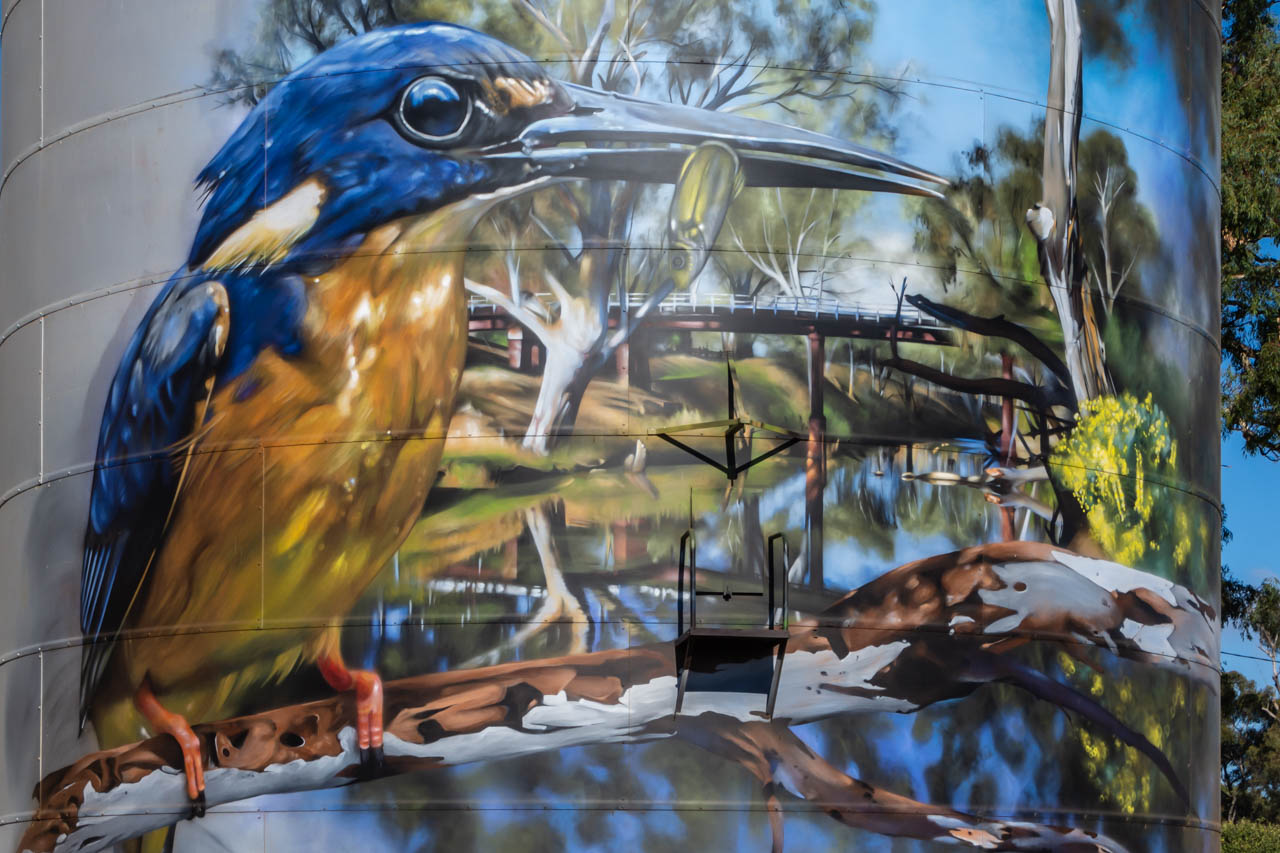 Painting of a blue and yellow bird, a river, and a bridge on a metal silo
